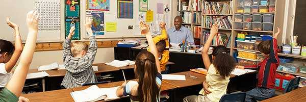 A classroom of students raising their hands