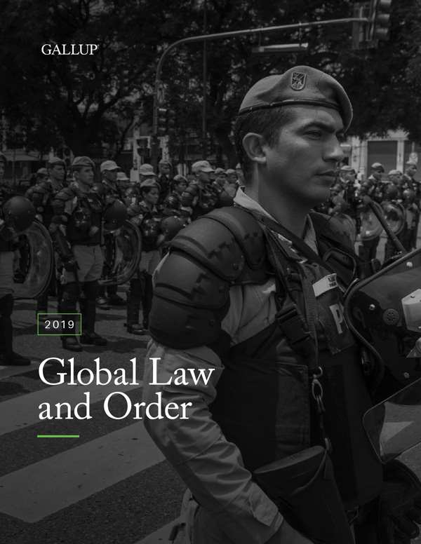 The cover of the 2019 Global Law and Order Report features a black and white image of police officer in tactical gear walking on the crosswalk on a street with many other soldiers in the background.