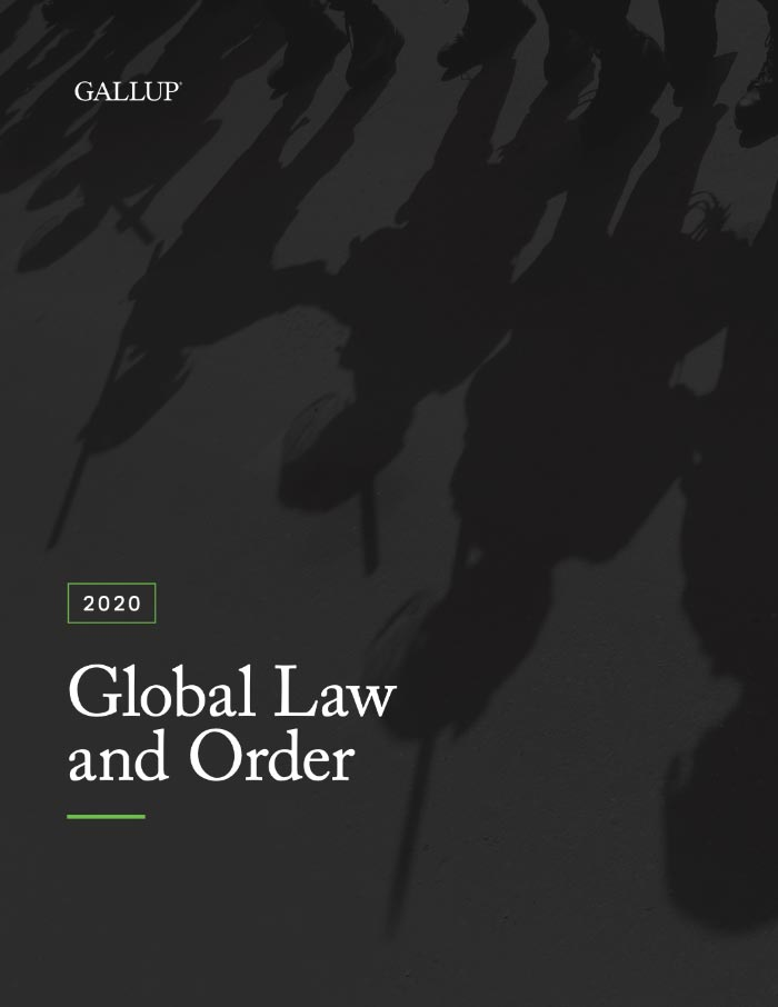 The feet of police force members are displayed with their shadow casting upside down on the cover of Gallup's Global Law and Order 2020 report. There are also shadows of weapons.