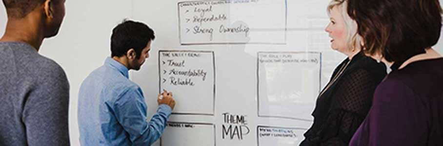 A man writing on a white board in front of a small group of people.