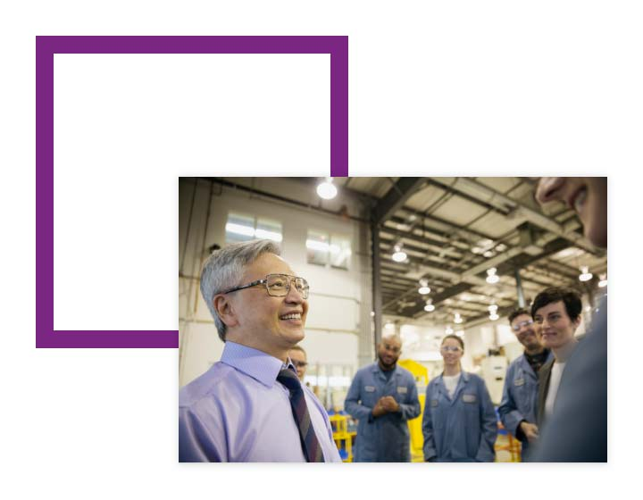 Image of warehouse workers talking over image of a purple square