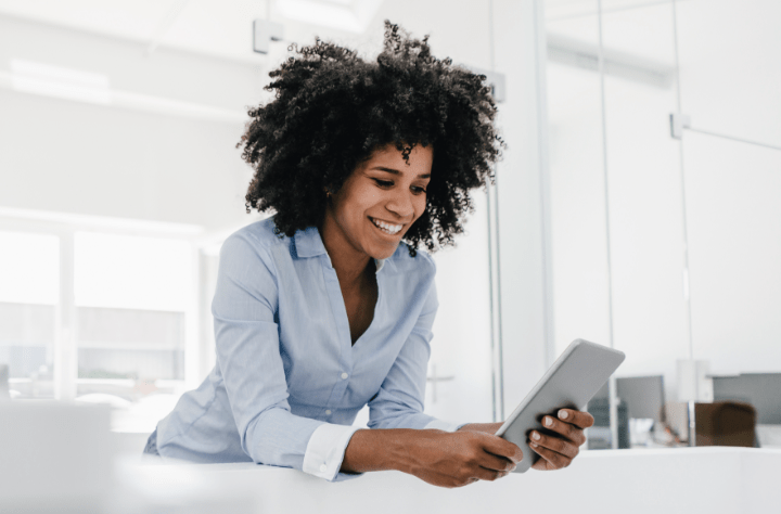 Smiling businessperson using a digital device in a sun-filled room.