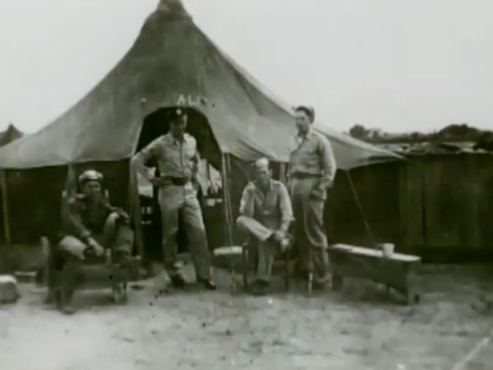 Don Cliton standing outside of a tent while serving in World War II