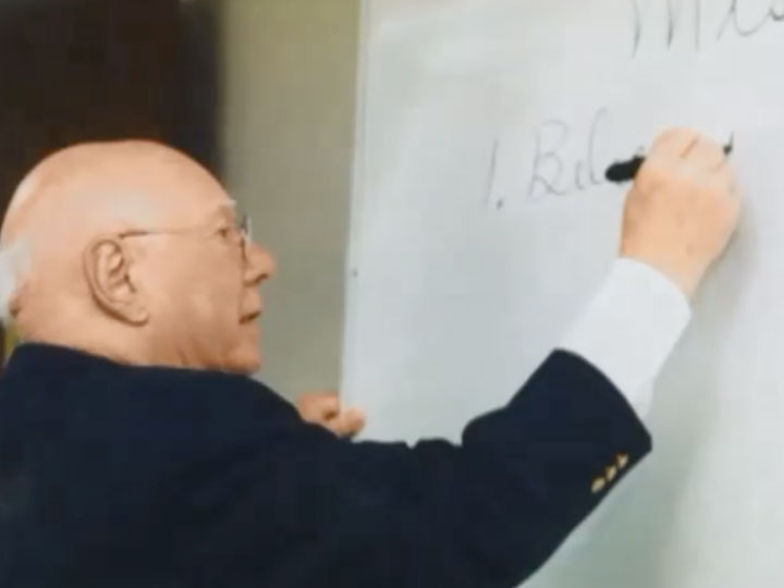 Don CLiton writing on a whiteboard while teaching a course at the University of Nebraska-Lincoln