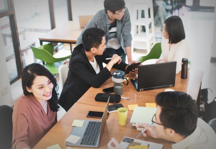图片7——人们围坐在一张桌子旁,用电脑和笔记本工作