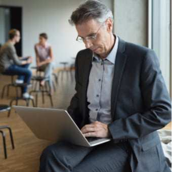 A man working on a laptop in an office environment.