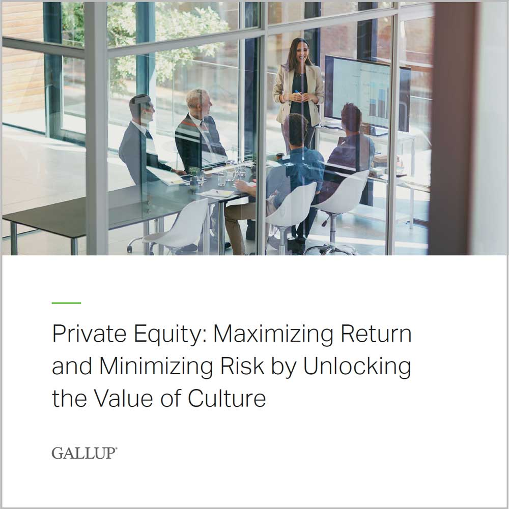 A woman makes a business presentation to a group of business leaders while they discuss the perspective paper: Private Equity: Maximizing Return and Minimizing Risk by Unlocking the Value of Culture