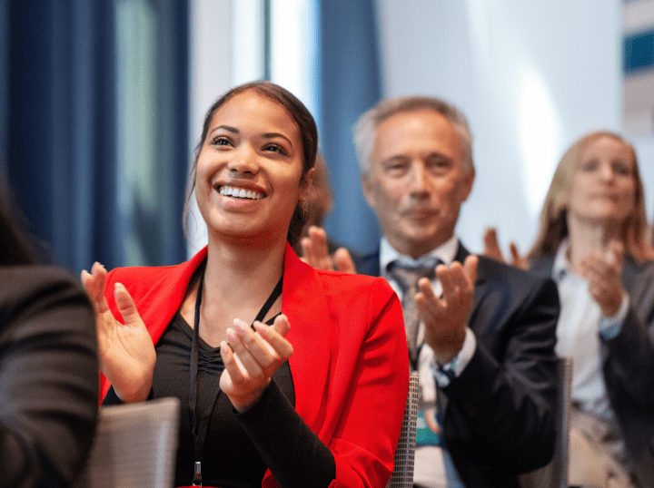 A woman in a red jacket clapping for engaged workplace winners.