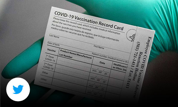 Blue gloved hand holding a blank covid-19 vaccination card.