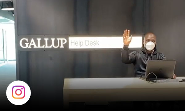 Man sitting down on stool at table waving to camera in front of Gallup Help Desk sign.