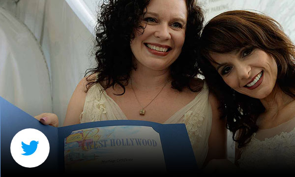 Two women in wedding dresses standing together holding up a marriage license.