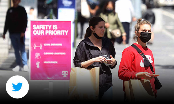 Two girls wearing masks carrying brown shopping bags with pink sign in background that reads safety is our priority.