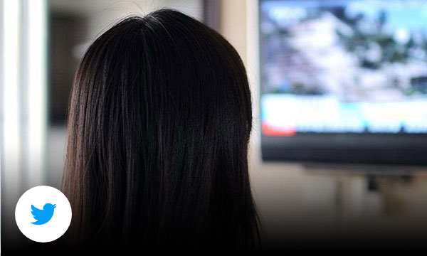 Back of a persons head watching a TV screen.