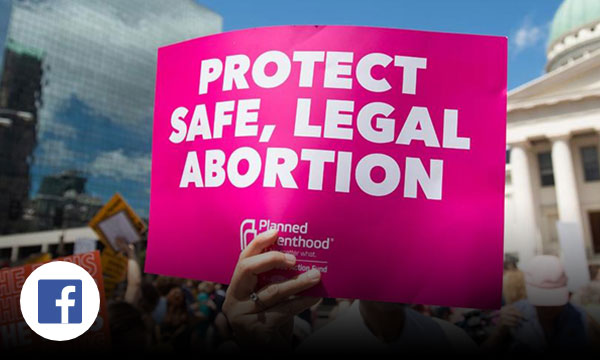 Capitol building in the background with pink sign being held up that reads protect safe, legal abortion.