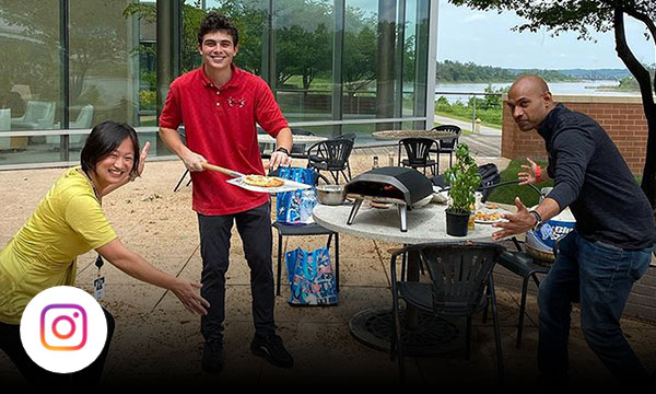 Three employees on the Gallup patio cooking together and showing a freshly baked pizza off to the camera.